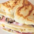 Torta de crepes caliente con espinacas y hongos cubierta con salsa de queso parmesano